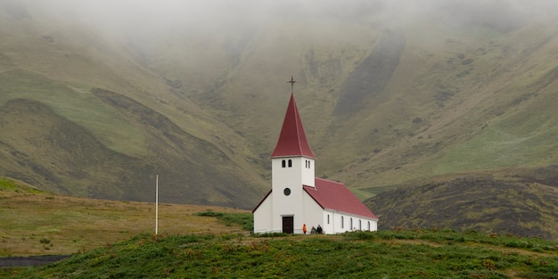 Ländliche kirche im grasbewachsenen tal mit nebel