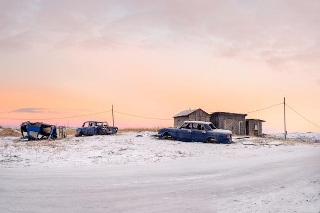 Ländliche landschaft des arktischen abends. alte zerlegte autos in den garagen im authentischen dorf teriberka. kola halbinsel. russland.