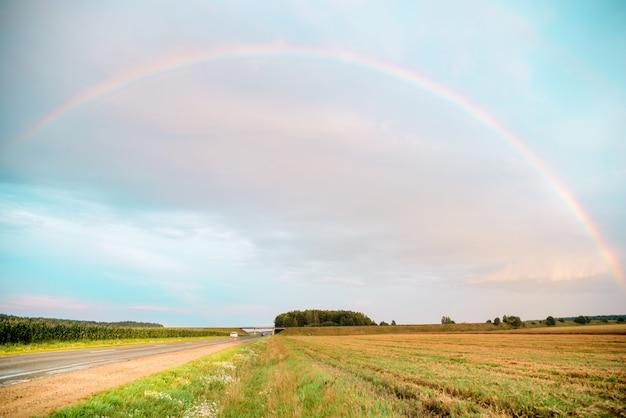 Ländliche landschaft des regenbogens mit weizenfeld auf sonnenuntergang