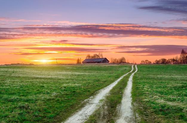 Ländliche landschaft, eine straße auf dem feld steigt zu einem hügel mit einer stehenden scheune während des abendlichen sommersonnenuntergangs.