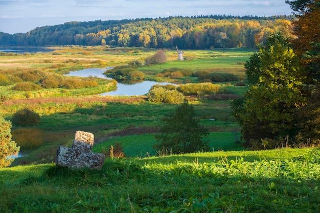 Ländliche landschaft mit blick auf den windmühlenfluss und die felder. puschkin-hügel mit savkina gorka. russland region pskow im frühherbst