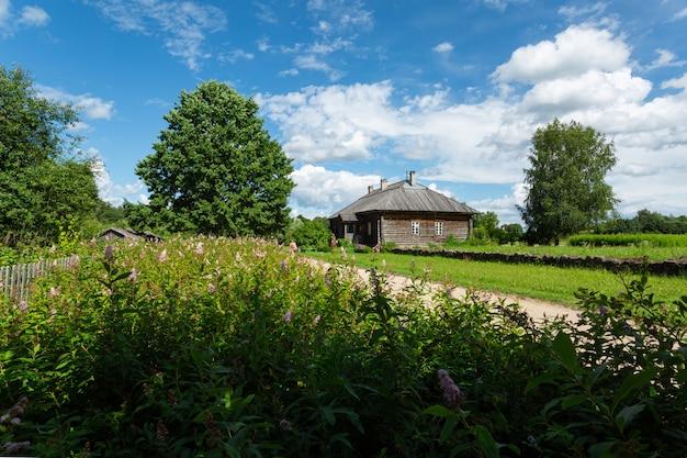 Ländliche landschaft mit dem holzhaus im feld an einem sonnigen tag.