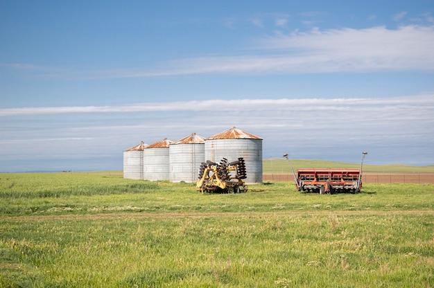 Ländliche landschaft mit einigen silos und landwirtschaftlichen maschinen