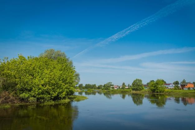 Ländliche sommerlandschaft mit fluss und blauem himmel.