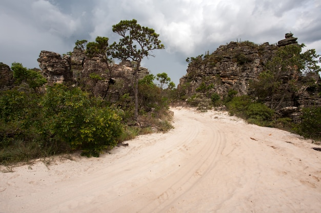 Ländliche unbefestigte straße mit sand und sandsteinfelsen