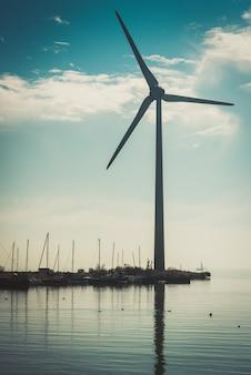 Ländliche wasserlandschaft mit arbeitswindkraftanlage