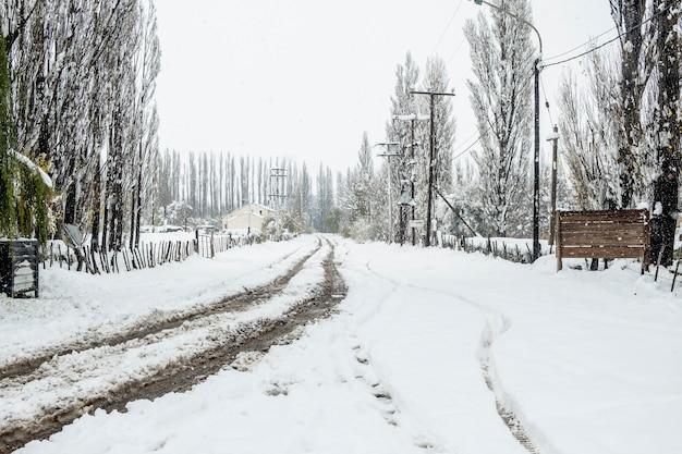 Ländliche winterlandschaft der schneebedeckten schotterstraße nach einem wintersturm