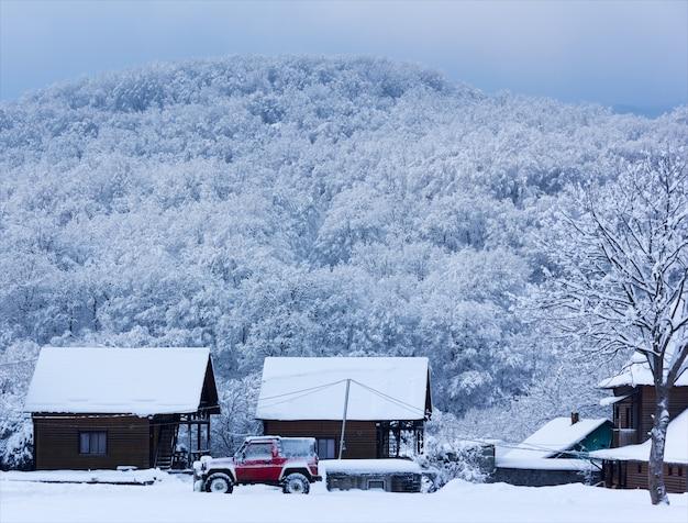Ländliche winterlandschaft. rotes suv auto im schnee nahe einem holzhaus auf einem hintergrund