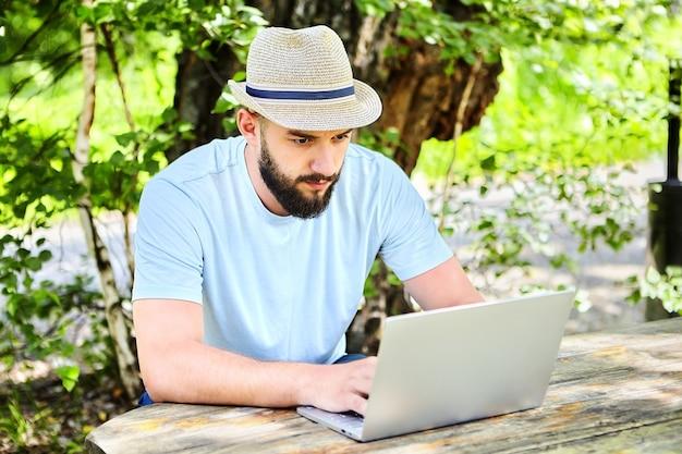Ländlicher geschäftsmann, agronomwissenschaftler studiert landwirtschaftsprogramm auf laptop.