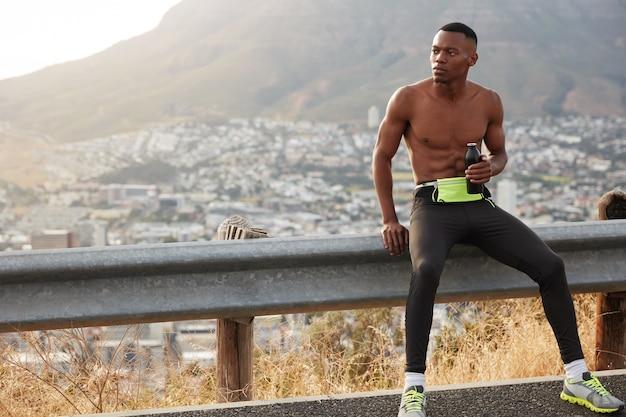 Ländlicher männlicher läufer mit dunkler haut, trinkt wasser und genießt pause, hatte aktives körperliches training während des heißen sommertages, ruht am straßenschild, erhält energie vom trinken felsiger berge