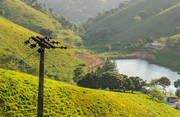 Ländlicher strommast im grünen mit see und bergen