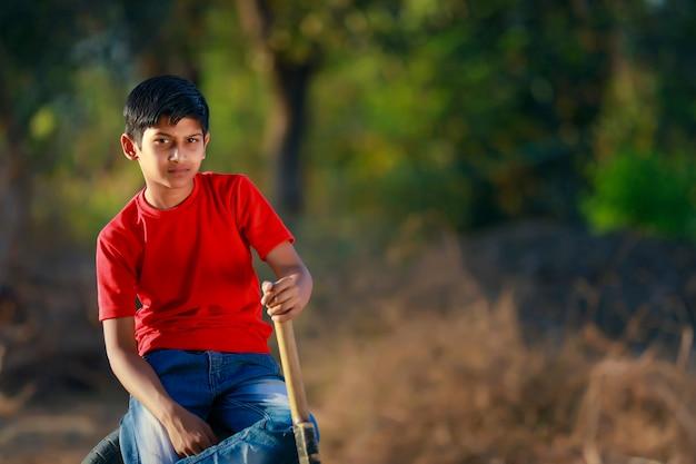 Ländliches indisches kind, das cricket spielt