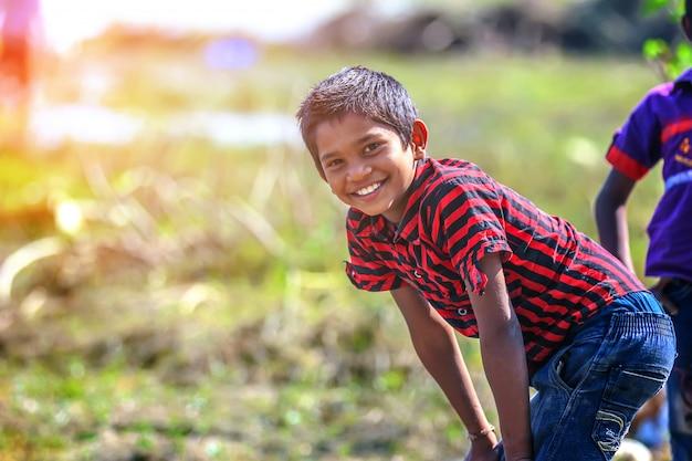 Ländliches indisches kind, das im fluss spielt