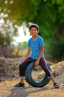 Ländliches indisches kind, das kricket auf dem boden spielt