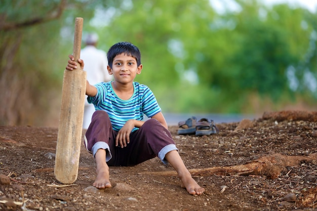 Ländliches indisches kind, das kricket spielt