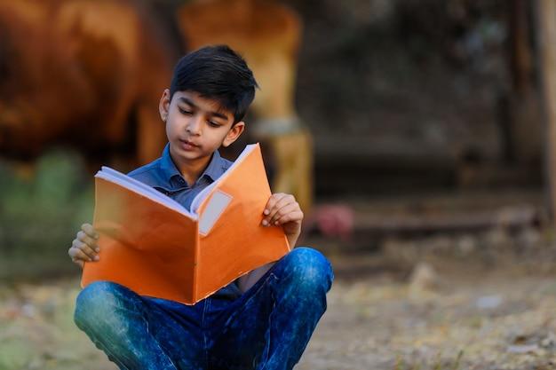 Ländliches indisches kind, das zu hause studiert