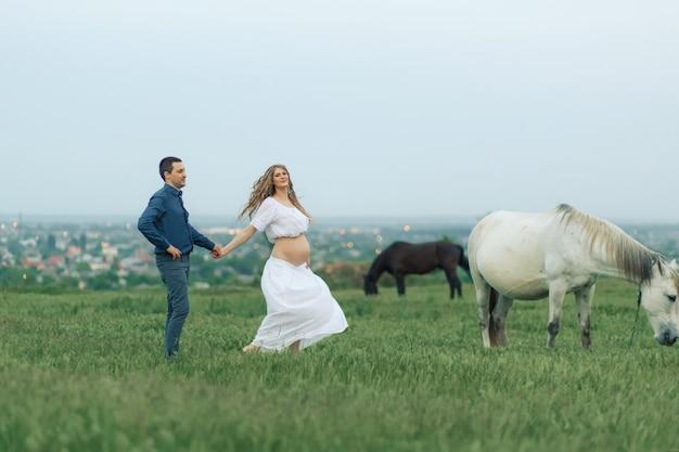Ländliches paar auf einer grünen wiese kommuniziert mit tieren. schwangere frau. therapie und entspannung für schwangere frauen.