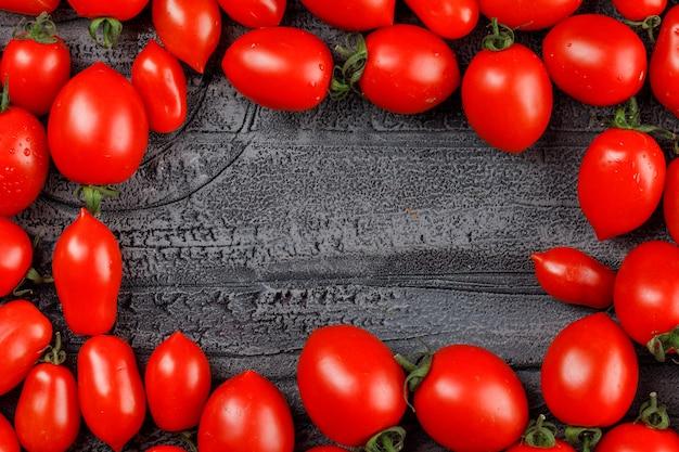 Längliche tomaten auf einer grauen schmutzwand.