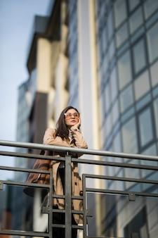 Lässig gekleidet schöne frau mit sonnenbrille bleibt auf der brücke