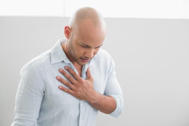 Lässig junger mann mit schmerzen in der brust