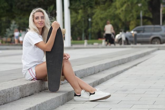 Lässige blonde frau in jeansshorts, die auf treppen mit longboard aufwirft.
