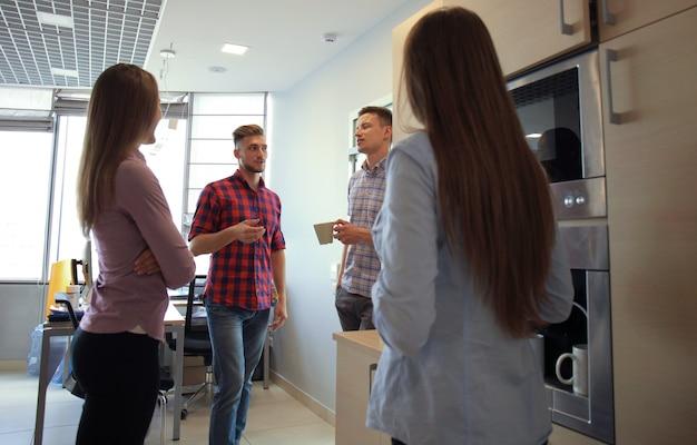 Lässige büroleute unterhalten sich an der kaffeemaschine
