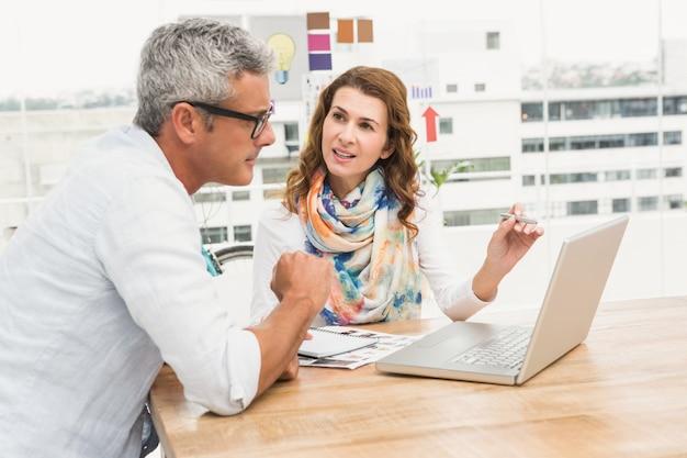 Lässige designer diskutieren und arbeiten mit laptop