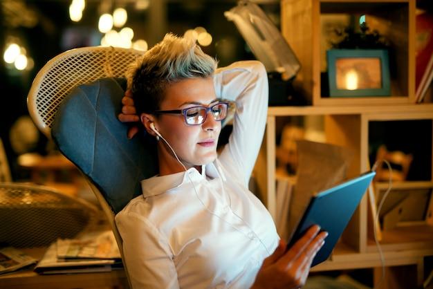 Lässige geschäftsfrau, die am sofa im café entspannt, lächelt und tablette betrachtet