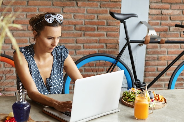 Lässige geschäftsfrau, die sonnenbrillen auf dem kopf trägt und auf dem laptop tastaturen trägt und während des mittagessens an ihrem freien tag e-mails abruft