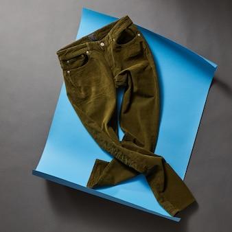 Lässige herrenoutfits mit herrenbekleidung auf blauem papier und schwarzer betonwand Premium Fotos