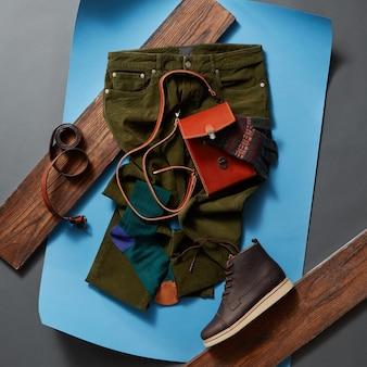 Lässige herrenoutfits mit herrenbekleidung und schuhen, accessoires auf blauem papier und holzbrettern