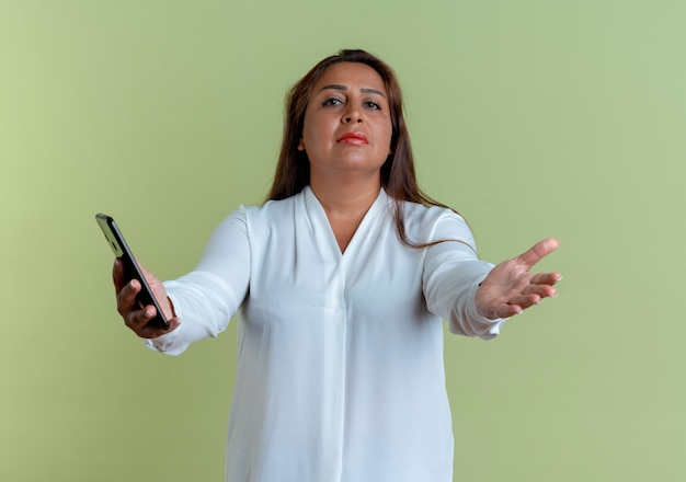 Lässige kaukasische frau mittleren alters, die telefon und hand nach vorne hält