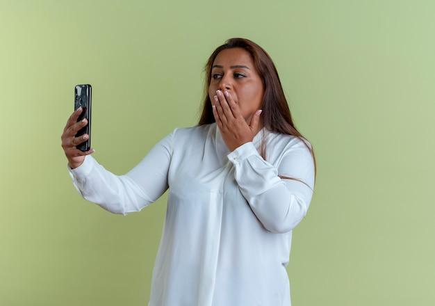 Lässige kaukasische frau mittleren alters nehmen ein selfie und bedeckten den mund mit der hand