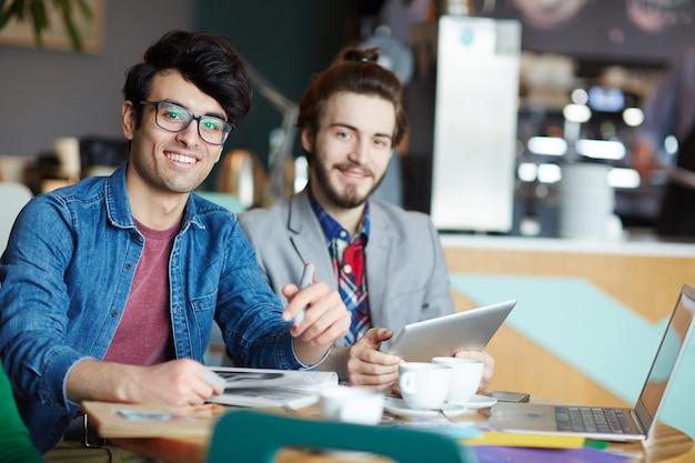 Lässige kreative geschäftsmänner, die im café sich treffen