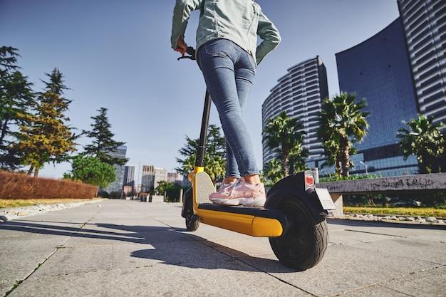 Lässige moderne frau, die elektroroller für umweltfreundliches fahren durch die stadt verwendet