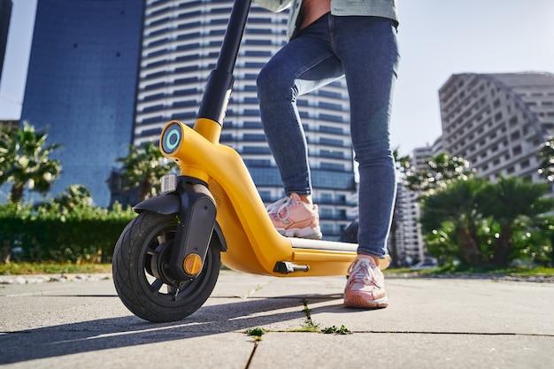 Lässige moderne frau mit elektroroller für schnelles umweltfreundliches fahren durch die stadt