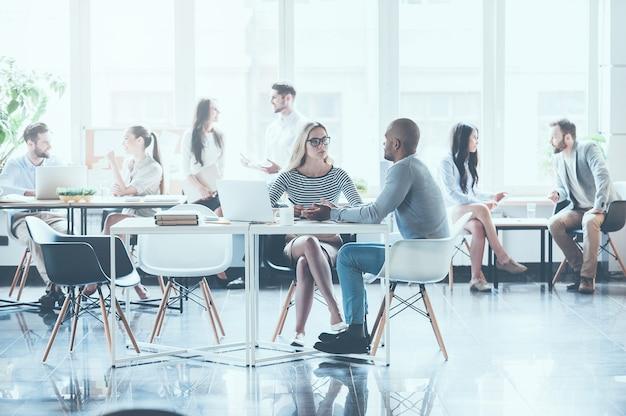Lässiger arbeitstag. gruppe junger geschäftsleute, die miteinander arbeiten und kommunizieren, während sie an ihren arbeitsplätzen im büro sitzen