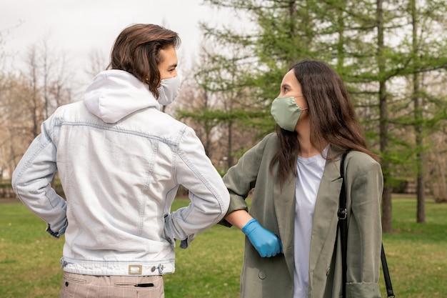 Lässiger junger freundlicher mann und frau in schützenden handschuhen und masken, die ellbogenstoß machen