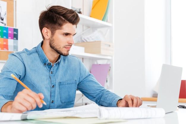 Lässiger junger geschäftsmann, der laptop betrachtet und mit dokumenten im büro arbeitet