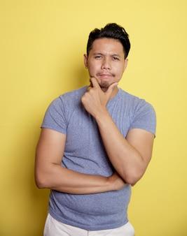Lässiger junger mann lächelt, der idee mit dem halten des kinns und einer hand auf magen lokalisiert auf einem gelben farbhintergrund denkt