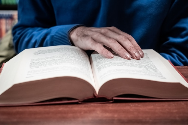 Lässiger mann, der buch auf holztisch in bibliothek, weinlesestil liest