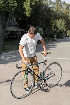 Lässiger mann der vorderansicht, der sein fahrrad prüft