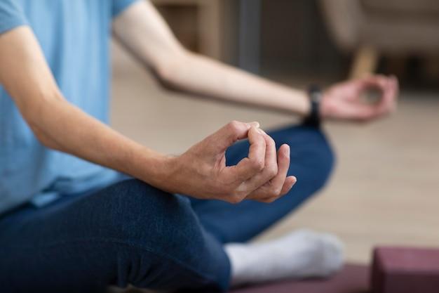 Lässiger mann, der zu hause yoga praktiziert