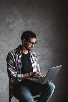 Lässiger mann mit laptop auf grau