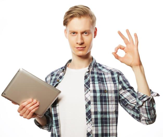 Lässiger mann mit tablet-pad-computer, der das ok-daumen hoch handzeichen macht