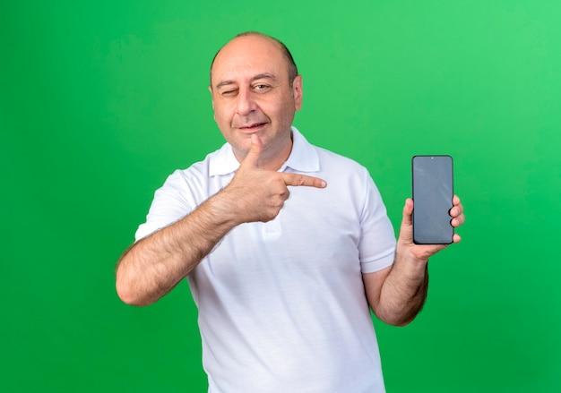 Lässiger reifer mann, der hält und auf telefon zeigt