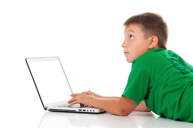 Lässiger teenager im hellgrünen t-shirt mit laptop auf weißem hintergrund