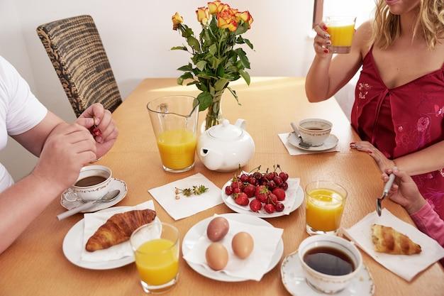 Lässiges frühstück einer jungen familie bestehend aus mutter, vater und kleiner tochter mit orangensaft, kaffee, tee, croissants