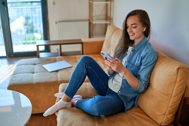 Lässiges, intelligentes, modernes, lächelndes tausendjähriges mädchen mit drahtlosem kopfhörer mit smartphone zum ansehen von videoinhalten, zum überprüfen von sozialen medien und zum online-shopping beim entspannen auf dem sofa zu hause