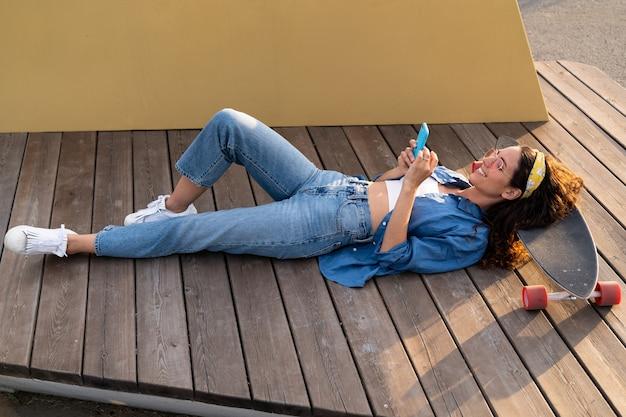 Lässiges junges hipster-mädchen mit sonnenbrille sms im smartphone im freien liegend entspannt im longboard